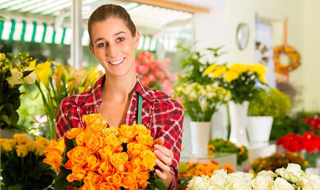 Floristin mit Blumen in Blumenladen